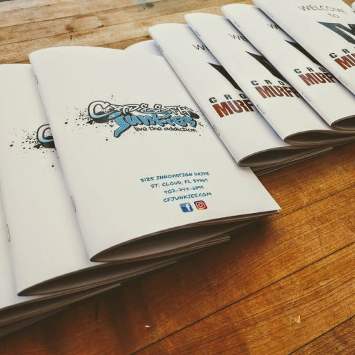Stack of Athlete handbooks customized for different gyms