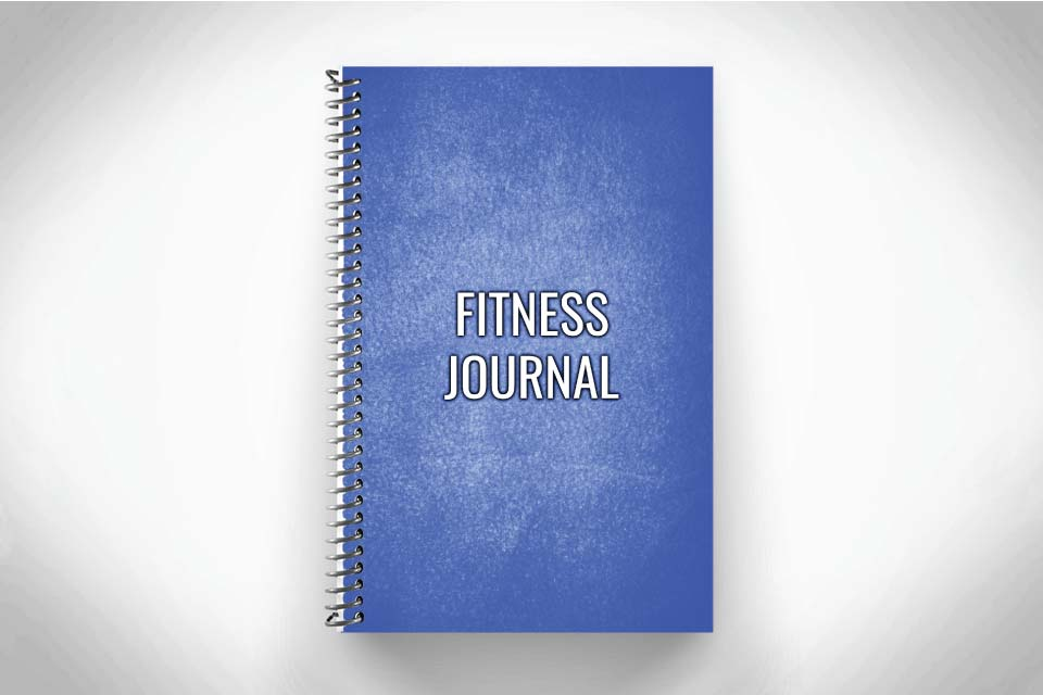 Blue fitness journal for strength and conditioning workouts on gray background