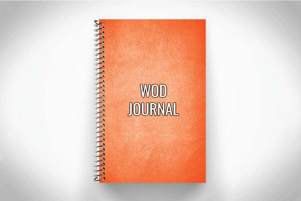 Orange WOD journal for crossfit workouts on gray background