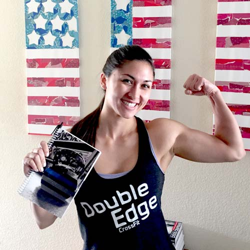 Black and white fitness journal held by strong female with american flag in background