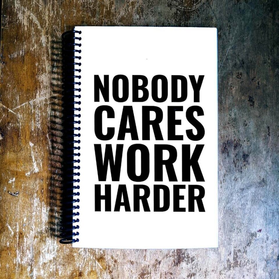 nobody cares work harder quote on white journal with wood table background