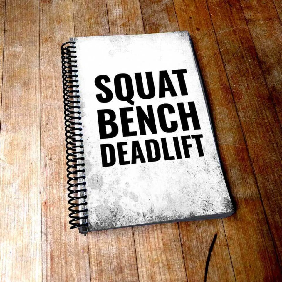 squat bench deadlift fitness motivation quote on distressed white journal cover sitting on wooden table